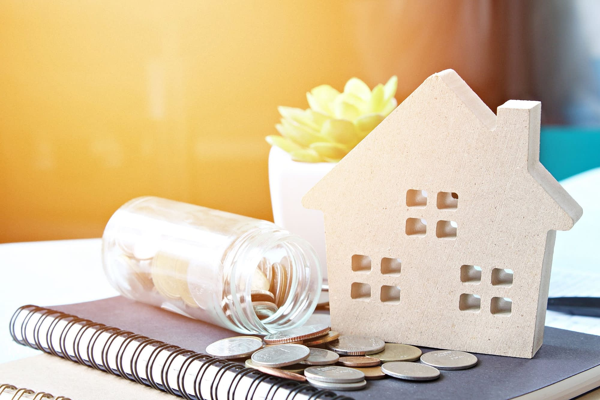 Toy house over coins and financial documents