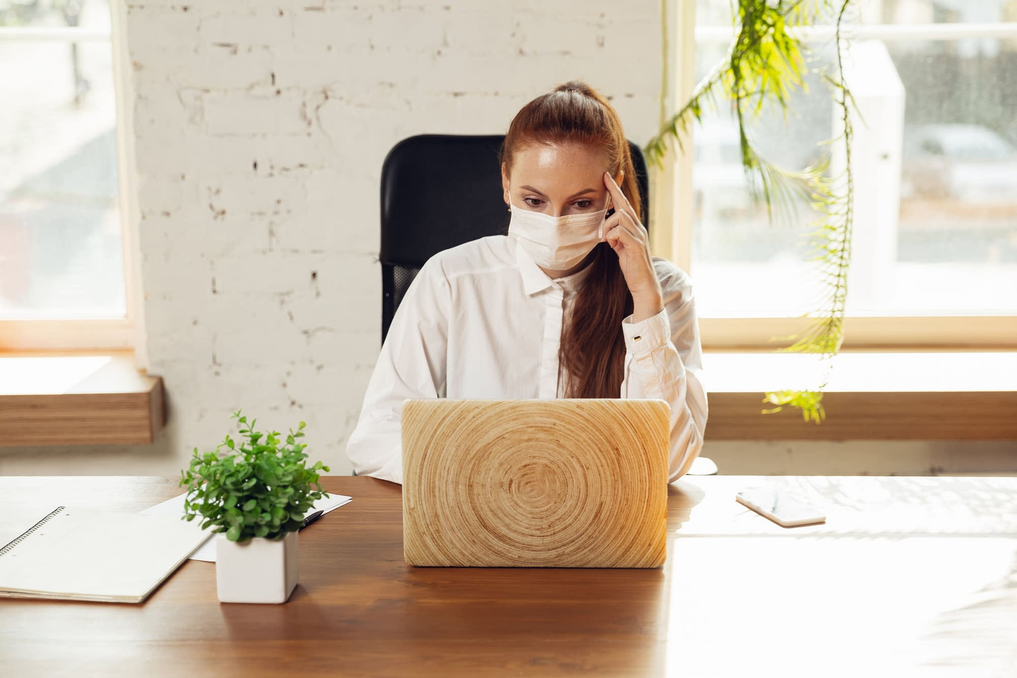 Getting info. Woman working in office alone during coronavirus or COVID-19 quarantine, wearing face mask. Young businesswoman, manager doing tasks with smartphone, laptop, tablet has online conference.