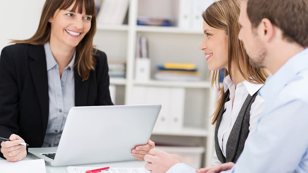 Young couple sitting in an office talking to a woman broker or investment adviser