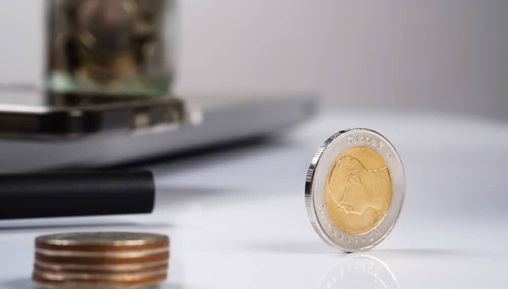 a gold and silver coin sitting up on its edge on a desk