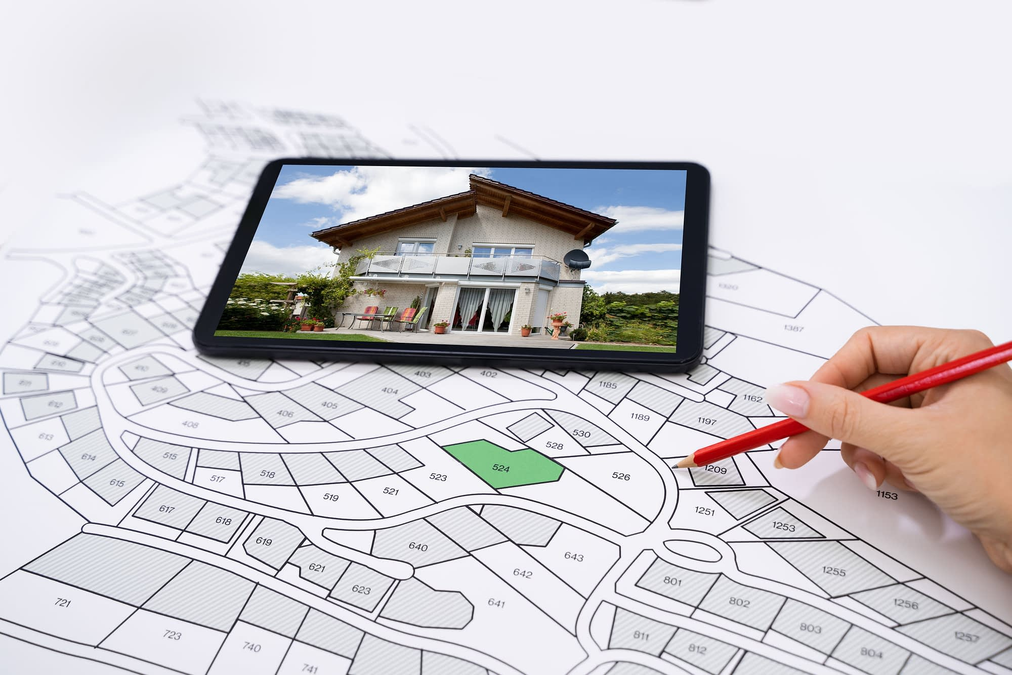 Hand Holding Pencil Over Cadastre Map New Tablet With House Photo