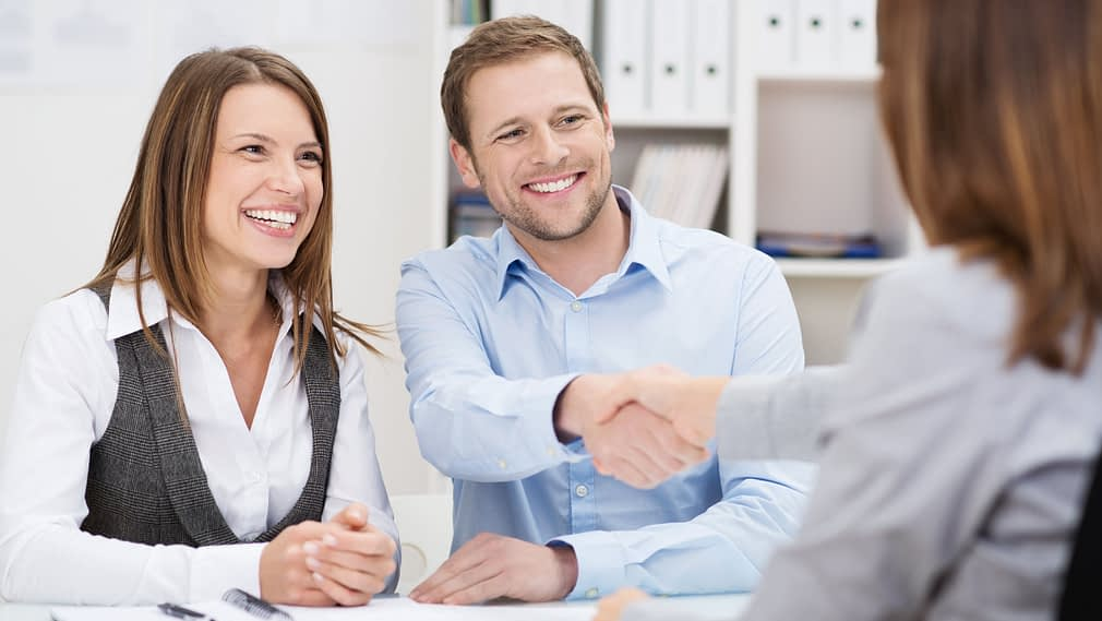 Smiling man shaking hands with agent