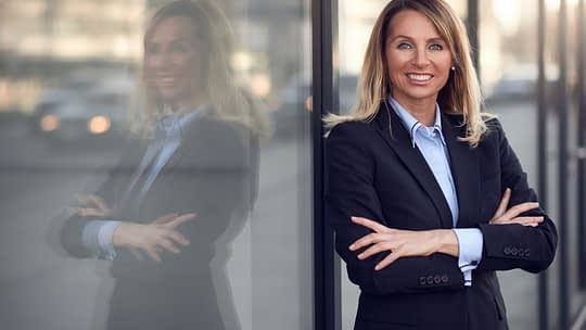 Single confident and attractive female businesswoman in blue suit with grin leaning on window outdoors