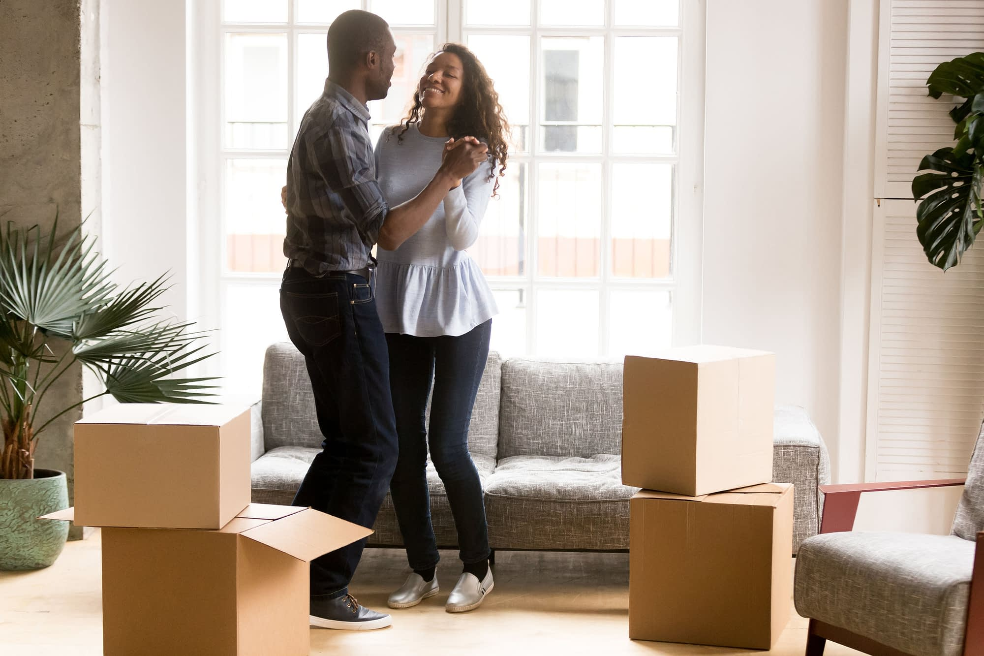 Happy African American couple in love dancing after moving in new house, attractive smiling woman and man celebrating relocating, cardboard boxes with belongings, homeowners in new apartment