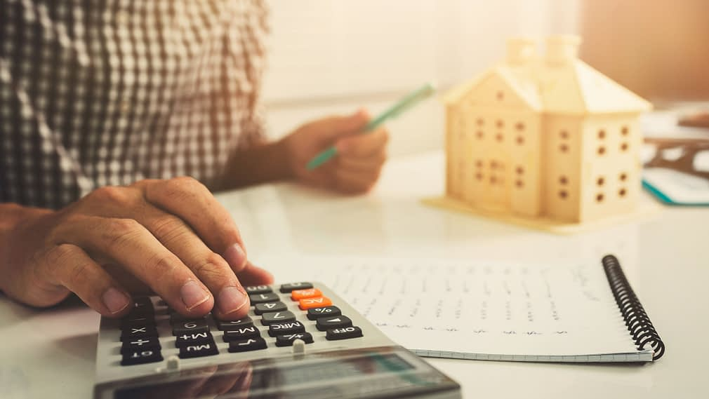 Young business man doing calculator finance cost in home office.