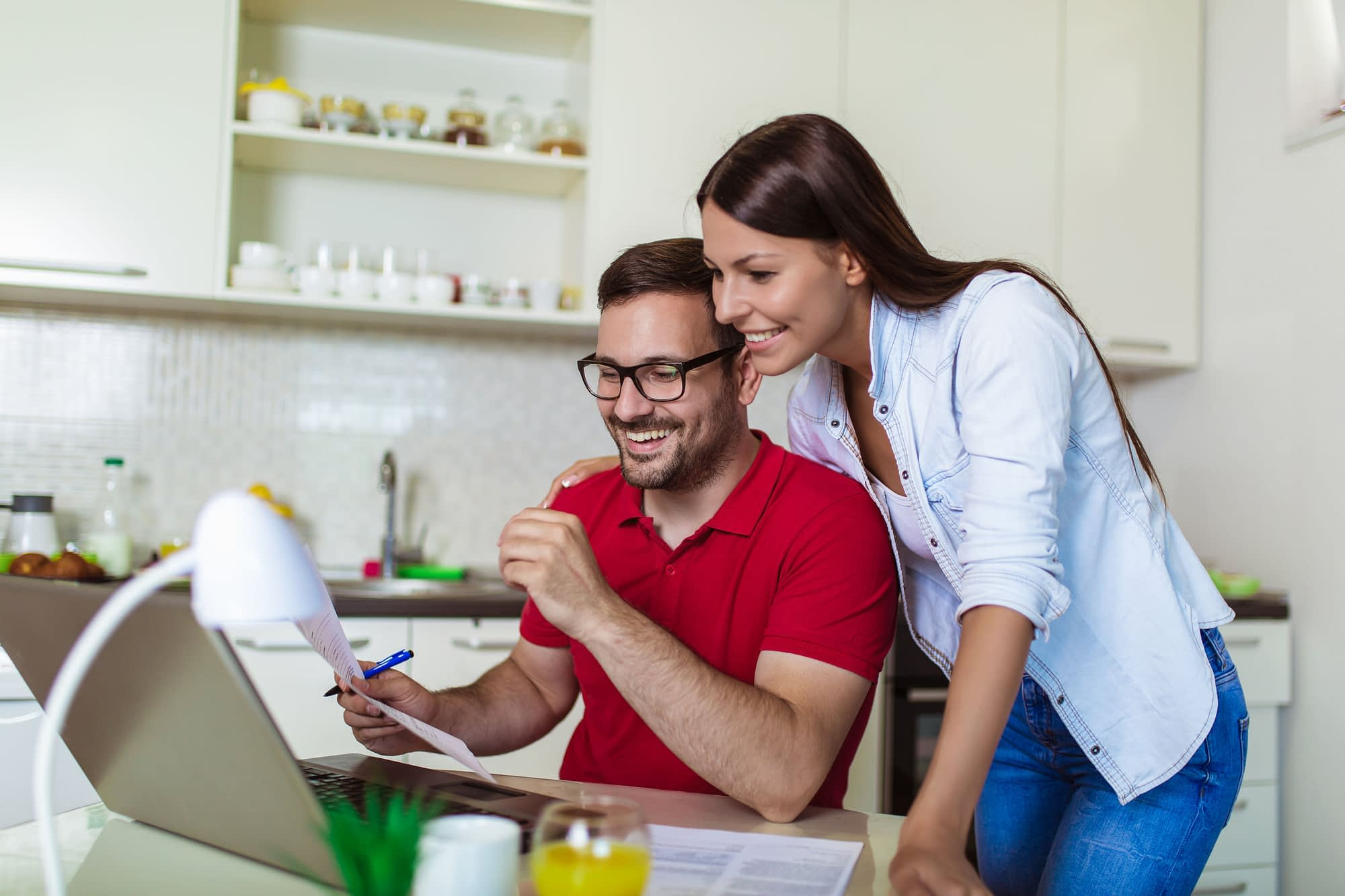 Young couple managing finances, reviewing their bank accounts with bank statements