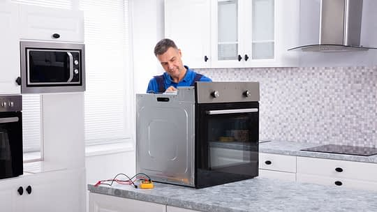 Mature Male Technician Repairing Oven On Kitchen Worktop with FHA 203(k) funds