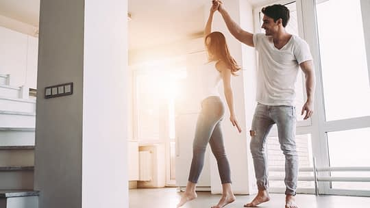 Happy couple dancing after purchasing non-warrantable condo