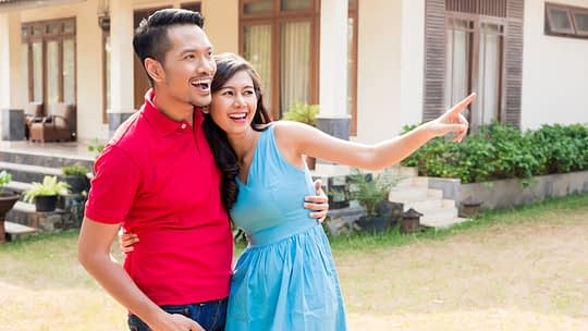 Cheerful young couple looking in the same direction in front of house